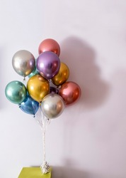 metallic coloured helium balloons tied with a bow and held by a weight on a green table, vertical format and copy space on the right