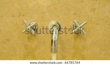 Metallic Faucet on yellow Ceramic wall with water drop