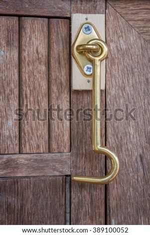 Metallic gold chromed hook with eye fixed on a closet
