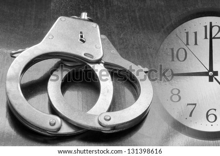 Metallic handcuffs on wooden table and clock