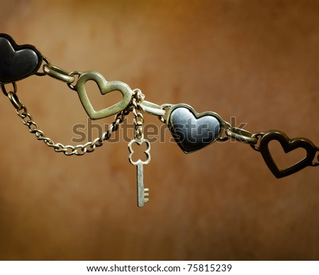 Metallic heart shapes and wrapped with gold chain metal key. On dark wooden background. Close-up.
