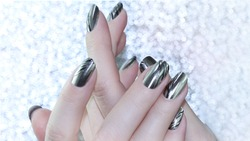 Metallic Nail design . Manicure nail paint . beautiful female hand with colorful nail art design manicure