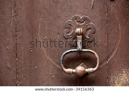 metallic old door knocker on wooden door