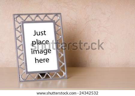 Metallic photo frame on a wooden shelf