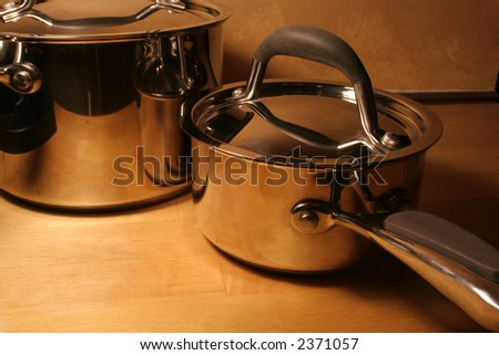 Metallic pots sitting on a wooden table.