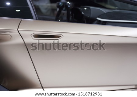 Metallic rose gold varnish car door with handle and window part as closeup at Autosalon Genf 2019 in Geneva, Switzerland