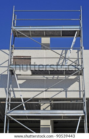 Metallic scaffold in a workplace. Security platform for working