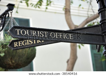 Metallic signpost indicating the direction of the tourist office