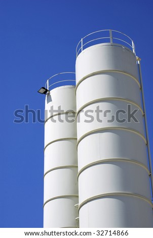 Metallic silos in white over the sky