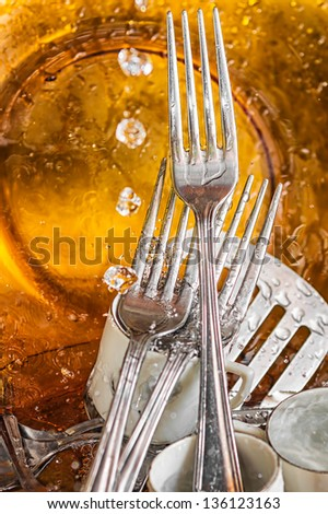 Metallic silverware and glass dishes washed under a water stream