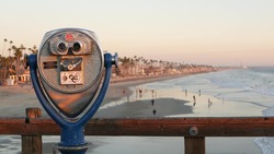 Metallic stationary observation tower viewer, waterfront old binoculars, Oceanside pier, California USA. Retro vintage beachfront coin operated telescope, sea coast outlook, summer ocean beach lookout