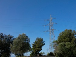 Metallic towers supporting the copper cables that carry electric power; towers over the blue sky: High voltage towers, engineering work to support the electric cable