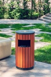 Metallic trash bin on the street, outdoors. Stainless steel litter bin with wood paneling, with a ashtray. Metal urn for mixed garbage and cigarette butts on the street of the city.