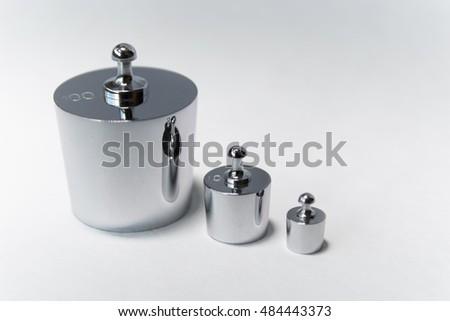 Metallic weights on white background. 100 g, 10 g, 2 g. #484443373