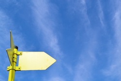 Metallic yellow arrow on blue sky background with white clouds