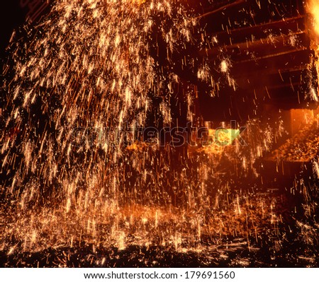 Metallurgic production, production of cast iron, metal melting. Fire sparks and molten metal splashes.