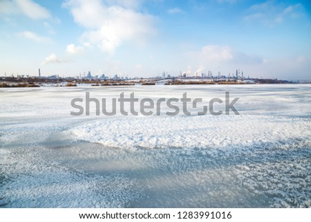 Metallurgy plant with smoke seen from the shore of a frozen lake. Steel factory with smog on winter day. Ecology problems, atmospheric pollution. #1283991016
