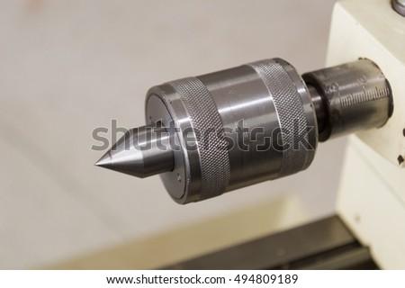metalworking industry: cutting steel metal shaft processing on lathe machine in workshop. Selective focus on tool #494809189