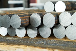 Metalworking of iron parts in a factory. Steel rods cut for further processing on a lathe.