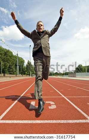 Metaphor for success in business - a business man crossing the finish line on an athletics track with his arms raised in victory