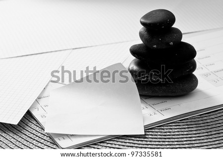 metaphor of balance in business: stacked zen stone on papers/calendar
