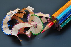 Metaphor of strategy and teamwork shown by color pencils with colred shavings on black background, representing the concept of thinking outside the box