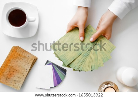 Metaphorical associative cards. Consultation of a psychologist. Young woman holds a deck in hands and chooses a card. Flat lay composition.