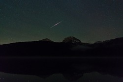 meteor in the night sky over a Black lake in the Durmitor National Park