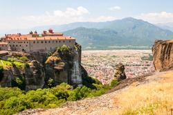 Meteora, Greece - June 16, 2013: Panoramic view on scenic Meteora landscape rock formations with Saint Stephen Nunnery Monastery on the cliff and Kalabaka town just above the mountain
