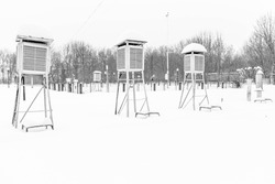 Meteorological booths for student training. High snow cover. Frosty weather with stratus clouds. Louver booth for meteorological instruments. Rain gauge and pluviograph.