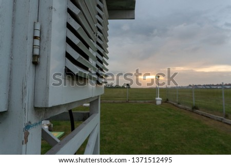 Meteorological cage under the grey cloudy sky. Meteorological cage is a place to put the meteorological tools like thermometer maximum, minimum, web bulb, dry bulb and etc. #1371512495
