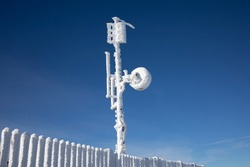 Meteorological Tower with measurement equipment, satellite dish, antenna. Device is covered by by frozen snow, ice and rime in cold and freezing winter. Sunny weather and clear blue sky.