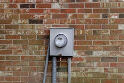 Meter base mounted to the outside wall of the house to measure the amount of electricity used.