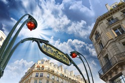Metro station sign in Paris with beautiful background sky.