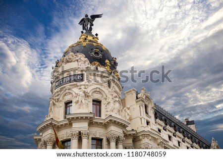 Metropolis - one of the most beautiful buildings in Madrid, Spain with dramatic blue cloudy sky on the background