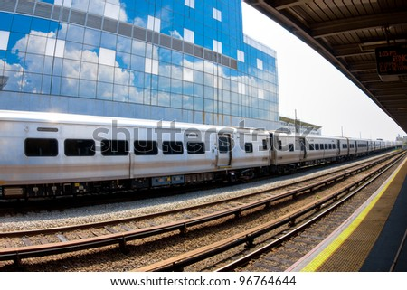 Metropolitan commuter train passing through the station with sky reflected in building behind.