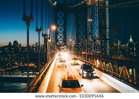 Metropolitan traffic on Brooklyn bridge with vehicles shining with evening light, yellow cab taxis driving from Manhattan to another district, River crossings, Environmental impact reduction concept