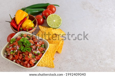 Mexican appetizer Pico de Gallo in a bowl and ingredients on the table. Homemade salsa sauce, great dip for nachos chips. copy space. Foto stock ©