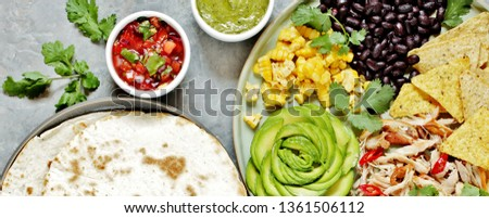 Mexican Buddha bowl with chicken meat fiber, black beans, corn, avocado rose, nachos corn chips. served with avocado sauce (avocado mayonnaise) and tomato salsa (Pico de Gallo) and tortillas