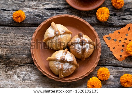 Mexican celebration, bread of death. Mexican parties Dead bread and marigold flowers on wooden rustic background. Traditional Mexican Bread of the Dead Pan de Muerto , Top view, Copy space.