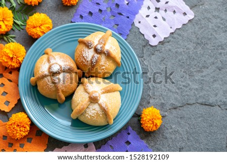 Mexican celebration, bread of death. Mexican parties with Dead bread and marigold flowers on gray stone background. Traditional Mexican Bread of the Dead Pan de Muerto .