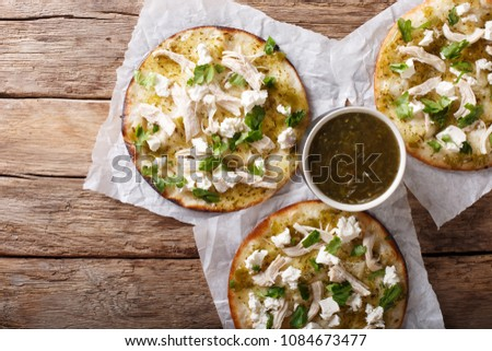 Mexican Chalupas with cheese and chicken meat and sauce salsa verde closeup on a table horizontal top view from above #1084673477