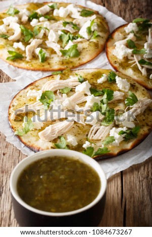 Mexican Chalupas with cheese and chicken meat and sauce salsa verde closeup on a table vertical  #1084673267