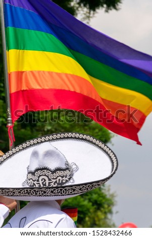Mexican charro waving gay rainbow flag during gay pride march in Mexico City