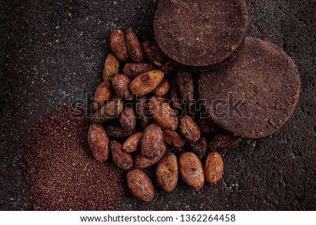 Mexican chocolate, cacao powder and cocoa top view, on a traditional metate. Cacao beans or cacao nibs are traditionally roasted in Oaxaca.