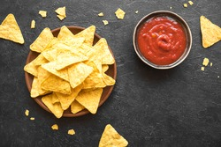 Mexican Corn Chips Nachos and traditional Salsa dip on black, copy space. Tortilla or Nacho Chips with tomato hot sauce for snack.