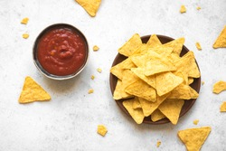 Mexican Corn Chips Nachos and traditional Salsa dip on white, copy space. Tortilla or Nacho Chips with tomato hot sauce for snack.