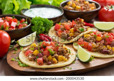 Shutterstock Mexican cuisine - tortillas with chili con carne and tomato salsa on wooden board, horizontal