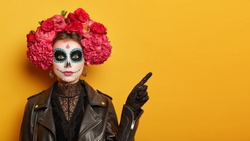 Mexican culture, Day of Death concept. Serious woman with bright scary makeup, flower wreath, dressed in black leather jacket, points aside on yellow copy space , shows place of Halloween party