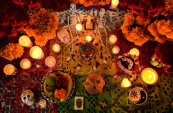 Mexican day of the dead altar at night in dim candlelight